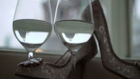 Woman`s white shoes and two glasses of champagne. Near window with reflections of cathedral stock video footage