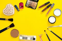 Woman`s workplace from top view on yellow background. Composition of beauty accessories for makeup and hygiene. Brushes, mascara, stock photography