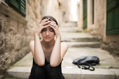 Woman with sad face crying.Sad expression,sad emotion,despair,sadness.Woman in emotional stress and pain.Woman sitting alone on th. E street with her things Royalty Free Stock Images