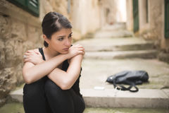 Woman with sad face crying. Sad expression, sad emotion, despair, sadness. Woman in emotional stress and pain. Woman sitting alone. On the stairs, after a fight stock photography