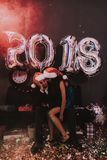 Woman with Sad Man in Red Cap on New Year Party. Happy New Year. Indoor Party. Celebrating of New Year. Young Woman in Dress. Young Man in Suit. Upset Man stock photo