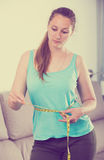 Woman sad to gain weight. Young woman having problems with weight gain at home Royalty Free Stock Image