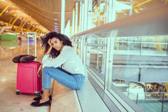 Woman sad and unhappy at the airport with flight canceled.  Royalty Free Stock Photography