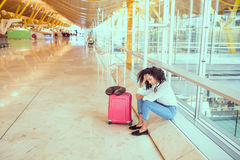 Woman sad and unhappy at the airport with flight canceled.  Royalty Free Stock Photo
