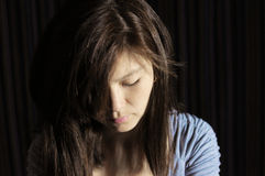 Woman in sadness loooking down. Studio shoot, dark background Royalty Free Stock Images