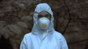 Woman in safety clothing and mask looking camera, exclusion zone, disaster