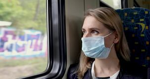 Woman with safety face mask sitting in train and looking through the window. virus pandemic