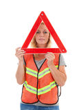 Woman in safety vest. Holding foldaway reflective road hazard warning triangle over white background stock photography