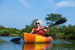 Woman With Safety Vest Kayaking Alone on a Calm River Stock Images