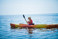 Woman With Safety Vest Kayaking Alone on a Calm Sea Royalty Free Stock Images