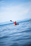 Woman With Safety Vest Kayaking Alone on a Calm Sea. Young Woman Kayaking Alone on a Calm Sea and Wearing a Safety Vest royalty free stock photos