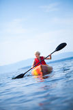 Woman With Safety Vest Kayaking Alone on a Calm Sea Stock Images
