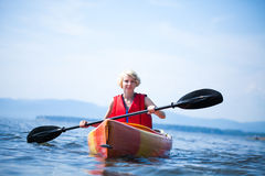 Woman With Safety Vest Kayaking Alone on a Calm Sea Stock Photography