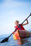 Woman With Safety Vest Kayaking Alone on a Calm Sea. Young Woman Kayaking Alone on a Calm Sea and Wearing a Safety Vest royalty free stock image