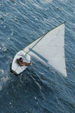 Woman in sailboat. Lone woman sailing in small craft stock photo