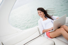 Woman sailing on a yacht with a laptop Royalty Free Stock Photos