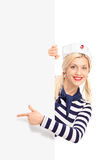 Woman in sailor outfit pointing on a billboard Stock Photography