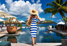 Woman sailor striped in dress near poolside. Woman in sailor striped dress near poolside jetty at Seychelles Stock Photo