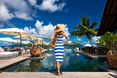 Woman sailor striped in dress near poolside. Woman in sailor striped dress near poolside jetty at Seychelles Royalty Free Stock Photo