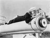 Woman in a sailors uniform lying on a cannon Royalty Free Stock Photo