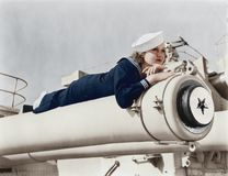 Woman in a sailors uniform lying on a cannon Stock Photos