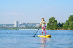 Woman sails on a SUP board on the cityscape background. Woman sails on a SUP board in large river on the cityscape background. Stand up paddle boarding - awesome stock images