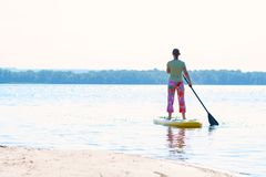 Woman sails on a SUP board in large river. On a sunny morning. Stand up paddle boarding - awesome active outdoor recreation. Back view stock photos