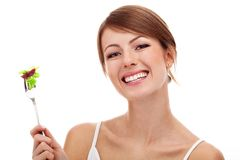 Woman with salad on fork, isolated. Woman with salad on fork, smiling. Isolated on white Royalty Free Stock Photography