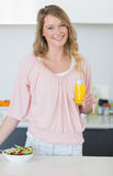 Woman with salad holding orange juice in kitchen Stock Images