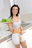 Woman with salad in kitchen Stock Photos
