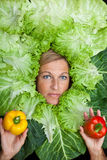 Woman with salal leafes around her head. Cute woman with salad leafes arranged around her head, whilde she is holding two bell pebers. Can be used for healthy Stock Photo