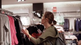 A woman at a sale picks t-shirts in a clothing store stock footage