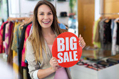 Woman with sale sign in clothes shop Stock Images