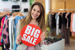Woman with sale sign in clothes shop Royalty Free Stock Photo