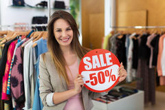 Woman with sale sign in clothes shop Stock Photography