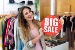 Woman with sale sign in clothes shop Stock Photos