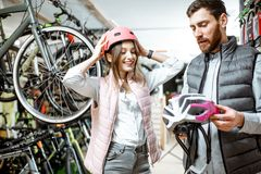 Woman with salesman in the bicycle shop. Young women customer choosing protective helmet standing with salesman in the bicycle shop stock image