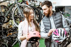 Woman with salesman in the bicycle shop. Young women customer choosing protective helmet standing with salesman in the bicycle shop royalty free stock photo