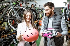 Woman with salesman in the bicycle shop. Young woman customer choosing protective helmet standing with salesman in the bicycle shop royalty free stock image