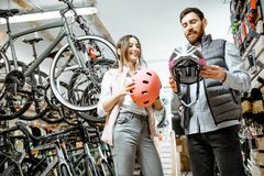 Woman with salesman in the bicycle shop. Young women customer choosing protective helmet standing with salesman in the bicycle shop stock images