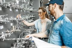 Woman with salesman in the plumbing shop. Young women choosing sanitary taps with salesman near the showcase of plumbing shop royalty free stock image
