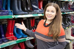 Woman salesman standing near store shelves and showing waterboots Royalty Free Stock Photo