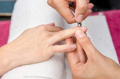 Woman in salon receiving manicure by nail beautician Stock Photos