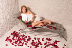 Woman in a salt room reading a book stock images