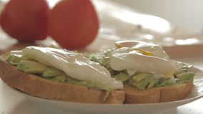 Woman salting healthy breakfast with avocado on roasted bread, eggs and tomato. Woman salting health breakfast in the kitchen in the morning hours by spreading stock footage