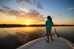 Woman Saltwater Fishing Casting From Boat During Sunrise. A woman casts a fishing line while saltwater fishing during the early morning in Southwest Louisiana royalty free stock image