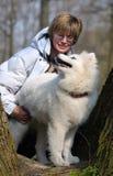 Woman and Samoed dog. At wall Royalty Free Stock Photo