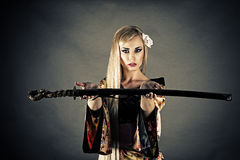Woman samurai sword gives. On gray background Stock Photos