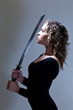 Woman Samurai Warrior. Pretty young woman with a samurai sword Royalty Free Stock Photo