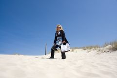 Woman on Sand Dune. Blonde woman in sunglasses standing on white sandy hill carrying large handbag Royalty Free Stock Image